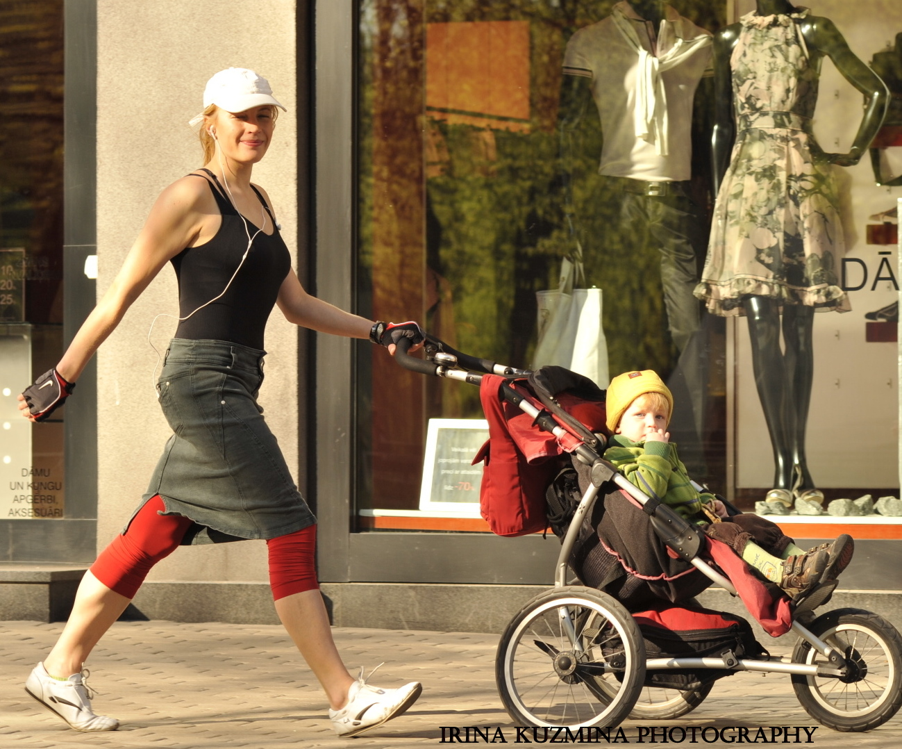 Sporty women walking fast with the jogging stroller